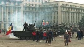 دبابة ومتظاهرون في مشهد من ثورة رومانيا ضد الحكم الشيوعي
