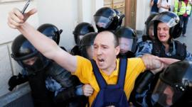 Russian riot police detain a protester