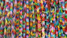 multi-coloured origami paper cranes hanging in vertical rows