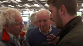 Two farmers chat to a reporter