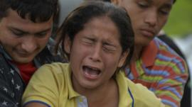 A woman mourns over the coffin of her father
