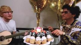 Ed Sheeran with a guitar, while Bruno Mars tucks into birthday cupcakes which spell out the word 'bruno'.