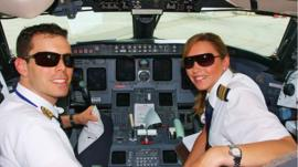 Young pilots flying in cockpit of commercial jet