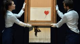 Sotheby's employees pose with the newly completed work by artist Banksy entitled Love is in the Bin