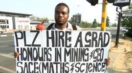 Jobless graduate Brian Radzuma holds a sign