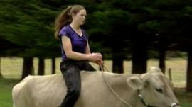 Hannah Simpson riding a cow