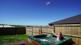 Man reaches for drone's load