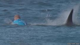 Surfer Mick Fanning in water with shark behind