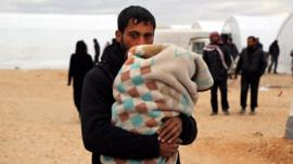 Syrians gather at a temporary refugee camp for displaced Syrians in northern Syria, near the Bab al-Salameh border crossing with Turkey