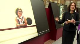 Head of Photographs at the Royal Collection Trust, Sophie Gordon, standing in front of a photograph showing the Queen laughing