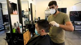 A man cuts hair while wearing medical gloves and a high-grade face mask in a hairdressers' shop
