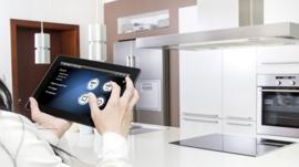 Woman using tablet to control kitchen appliances