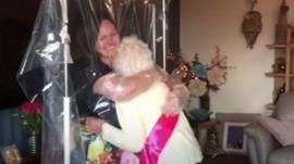A grandma hugging her granddaughter through a curtain