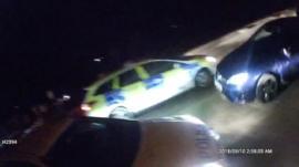 Car driving towards police cars