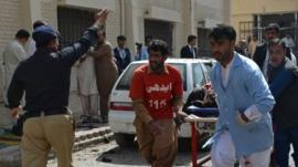 Pakistani volunteers rush an injured person for medical help following a bomb blast in Quetta, Pakistan