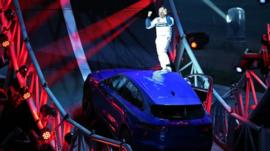 Driver Terry Grant stands on a Jaguar F-PACE after he drove round a giant loop the loop track on September 14, 2015 in Frankfurt, Germany.