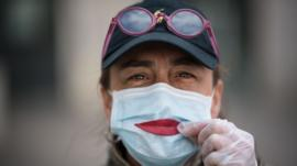 A woman wearing a protective mask holds a leaf as a smile in France, on 29 March 2020