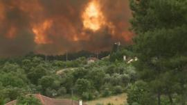 A wildfire rages in central Portugal affecting houses and a wooded area.