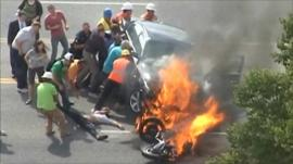 Passers-by lifting the car as the victim is pulled to safety