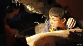 13 year old boy waiting to be rescued from rubble