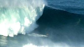 Surfer rides gigantic wave