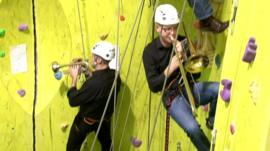 students playing instruments while climbing a wall