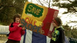 Children hold up 'Save Our Slope' sign