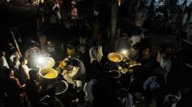 Pakistani vendors sell food under the lights of gas lamps during a power cut in Lahore