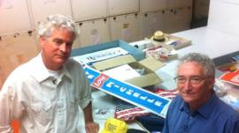 Larry Bird and Harry Rubenstein standing alongside materials they picked up at political rallies in the US
