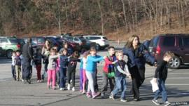 Police personnel lead children from the Sandy Hook Elementary School