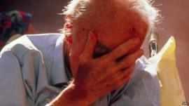 elderly man covering his face