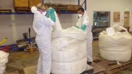 Bags of drugs being taken out of larger sacks