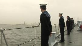 The crew of HMS Edinburgh on deck, with the Statue of Liberty visible in the distance