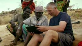 Richard Gibson shows Samburu farmers his cows on a laptop