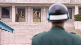 A South Korean soldier and his North Korean counterpart look at each other across the border