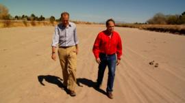 Men walk in dried up Rio Grande River