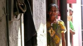 A Sri Lankan woman standing outside her house