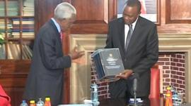 Uhuru Kenyatta receiving the report