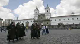 Nuns walking across the central square in Quito