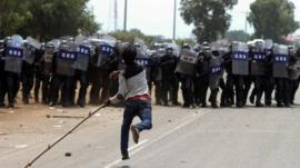 A protester throws a stone at riot police during clashes in front of a factory owned by Sabrina