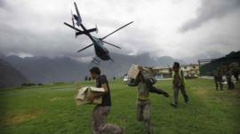 Indian civilians get ready to load relief material for flood affected victims on a helicopter at a makeshift helipad at Joshimath, in northern Indian state of Uttarakhand,