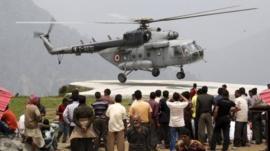 Stranded people rescued by the armed forces from Gaurikund watch a helicopter in Uttarakhand