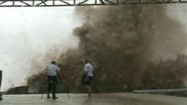 Two people photograph a wave