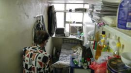 Man enters his small home in Hong Kong