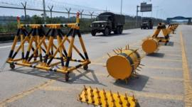 South Korean military trucks drive past barricades on the road linking North Korea's Kaesong Industrial Complex