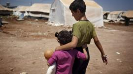 Syrian childen walking in refugee camp