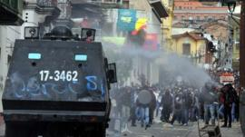 Riot police tanks try to disperse protesters with a water cannon