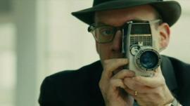 Actor Paul Giamatti as Abraham Zapruder with movie camera