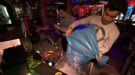 Barman putting ice in a bucket