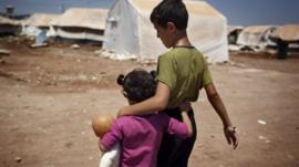 Syrian refugee children walk in the Bab al-Salam refugee camp in Syria's northern city of Azaz